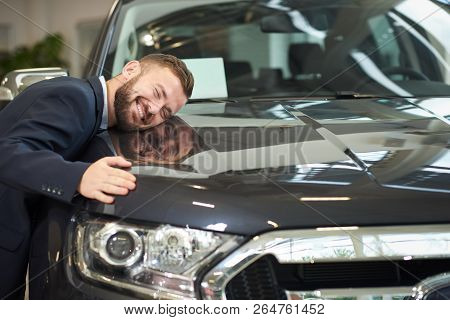 Front View Of Dark Blue Car, Headlight And Man Lying On Car Hood And Hugging Auto. Happy Owner Of Ne