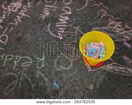 Yellow Bucket Filled With Multi Colored Chalk On A Sidewalk Filled With Words And Heart Drawings