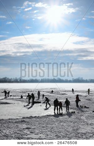 Ice-skating on frozen lake behind sunny of the day