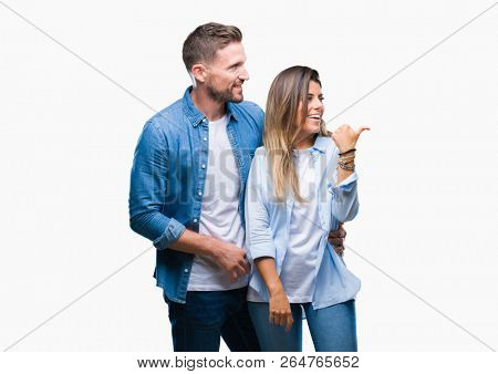Young couple in love over isolated background smiling with happy face looking and pointing to the side with thumb up.