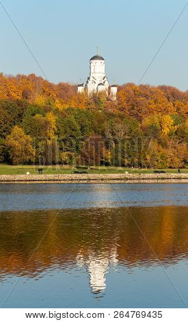 Colorful autumn. Alley along the riverbank on the background of the autumn park. Reflections in the