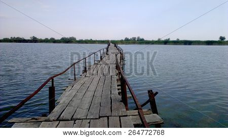 Old Bridge Over The Lake. An Old Broken Wooden Bridge Across The Lake. This Old Bridge Connects The