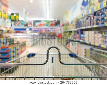 View From Shopping Cart Trolley Basket At Supermarket Self-service Grocery Shop. Retail. Blurred Bac
