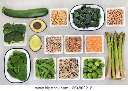 Protein plant super food selection for a healthy diet with seeds, grain, legumes and vegetables on rustic wood background. Health foods high in fiber antioxidants, vitamins and minerals. Top view.
