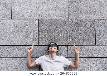 Cheerful Guy Dressed In Gray T-shirt, Sunglasses And Hat At The Street, Show A Big Sale, Or Nice Off