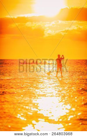Hawaii ocean lifestyle - watersport activity on ocean - stand up paddleboard, people training on outrigger canoe . Active summer healthy living. Silhouette of standing person doing paddle board.