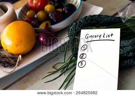 Grocery List Shopping List On Kitchen Counter With Healthy Vegetables, Kale, Tomatoes, Fruit, Fresh
