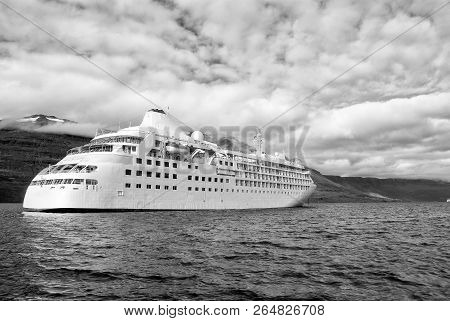 Ocean Liner In Sea On Mountain Landscape In Sejdisfjordur, Iceland. Cruise Ship In Sea With Mountain