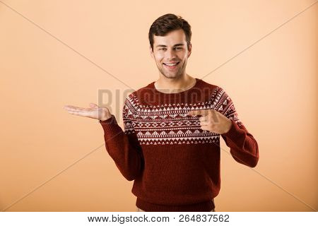 Image of good-looking man 20s with bristle wearing knitted sweater pointing finger at copyspace on palm isolated over beige background