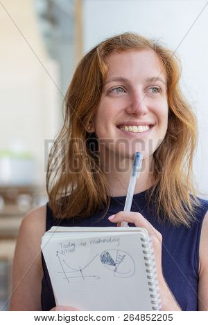 Cheerful Manager Thinking Over Business Strategy. Young Woman In Casual Writing Diagrams And Graphs