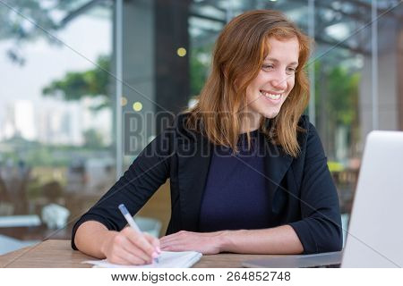 Positive Manager Interacting With Customer Via Video Call. Young Woman In Jacket Smiling At Laptop S