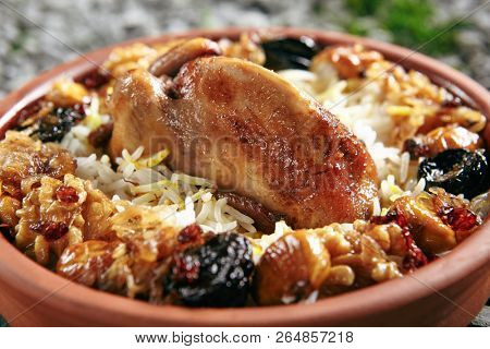 Beautiful Serving Vintage Ceramic Bowl of Lyavangi or Lavangi with Roast Quail with Rice and Chestnuts Close Up. Whole Chicken Pilaf or Wildfowl Stuffed with Walnuts, Onions and Various Condiments