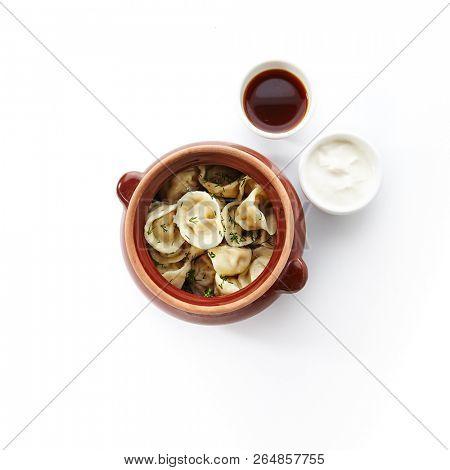 Dumplings with Minced Meat also known as Pelmeni, Gyoza, Dim Sum, Jiaozi, Momo, Tortellini, Pierogi, Varenyky, Mandu or Ravioli in Rustic Clay Ceramic Pot With Sauce and Sour Cream on White Background