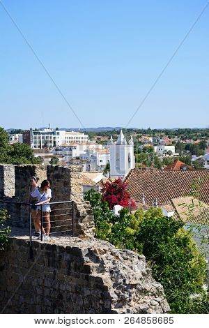 Tavira, Portugal - June 12, 2017 - Two Young Women Standing On The Castle Battlements With Town Buil