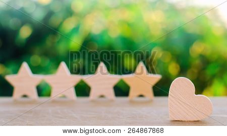 Four Stars And Heart On A Green Bokeh Background. Rating Five Stars, The Choice Of The Editorial Off