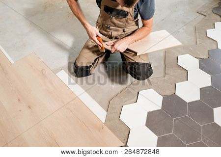 Male Worker Installing New Wooden Laminate Flooring. The Combination Of Wood Panels Of Laminate And