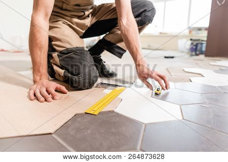 Male Worker Makes Measurements And Installing New Wooden Laminate Flooring. The Combination Of Wood