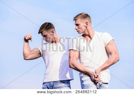 Men Twins Brothers Muscular Guys Sky Background. Men Strong Muscular Athlete Bodybuilder Posing Conf