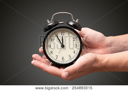 Hand Holding Clock With Five Minutes To Twelve O'clock