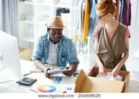 Young woman packing order into the box with man using touchpad to do delivery to the client