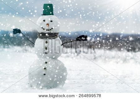 Tall Smiling Snowman With Green Bucket Hat, Scarf And Gloves On Tree Branch Hands On White Snowy Win