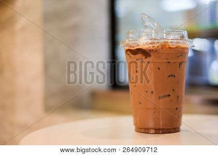 Lce Cocoa Or Coffee In Plastic Glass On Wooden Table For Relax & Background Or Texture.