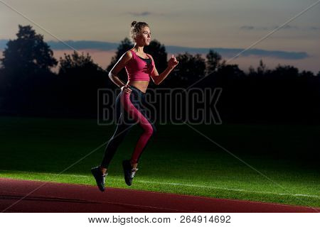 Side View Of Pretty And Athletic Girl In Stylish Black And Pink Sport Wear Running At Night On Stadi