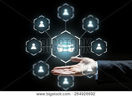 business, rental service and future technology concept - close up of businessman hand with virtual hologram of car sharing over black background