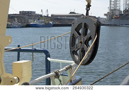 A Steel Pulley Hanging From A Ship With Ropes Attached Through It In The Harbor On A Sunny Day