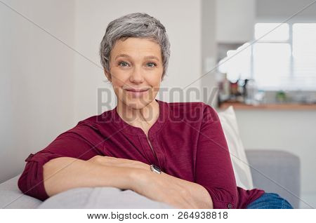Happy mature woman relaxing on her couch at home in the living room. Closeup face of senior woman looking at camera. Portrait of happy lady with gray hair smiling.