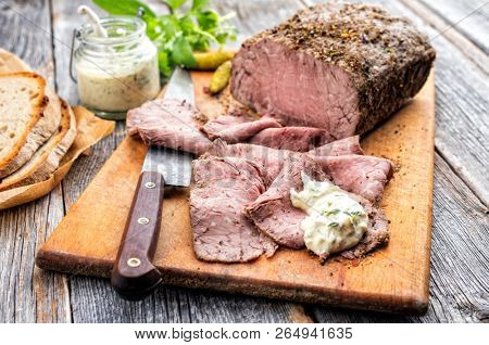 Traditional lunch meat with sliced cold cuts roast beef, remoulade and farmhouse bread as closeup on a cutting board