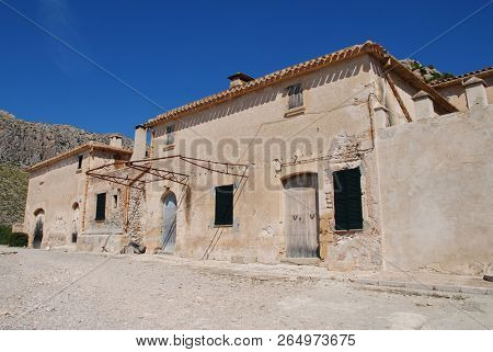 MAJORCA, SPAIN - SEPTEMBER 30, 2018: The old farm buildings at the entrance to the Boquer valley walk in Puerto Pollensa. The 3km trail leads though the Tramuntana mountains to Cala de Boquer.