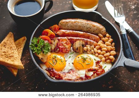 Full English breakfast - fried egg, baked beans, bacon, sausages on a dark rusty background, toasts, orange juice and coffee on a side. Dish in iron frying pan.