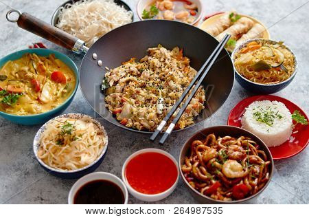 Chinese food set. Chinese noodles, fried rice with chicken, tom yum soup, spring rolls, deep fried fish and udon. Top view. Asian style food concept composition.