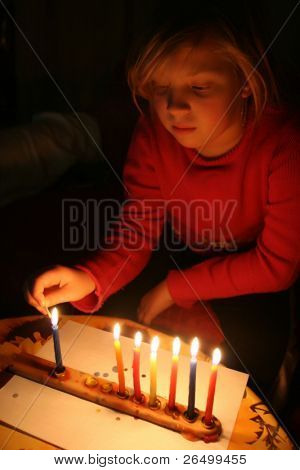 A girl lights a candle in the Jewish holiday of Hanukkah