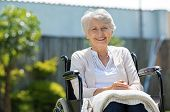 Happy senior woman sitting on wheelchair and recovering from illness. Handicapped mature woman sitting in wheelchair looking at camera. Portrait of a disabled elderly woman outdoor in a nursing home. poster