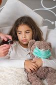 A little girl with a favorite teddy bear on whom they put on a gauze bandage is lying sick in bed and her mother is drinking her medicine. poster