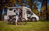 Woman on electric bike resting at the campsite. Family vacation travel, holiday trip in motorhome, VR Caravan car Vacation. poster