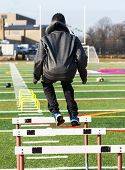 A high school boy is jumping over track hurdles with yellow mini hurdles and medicine balls in front of him for speed and agility practice. poster