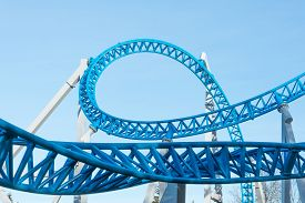 Loop And Turn On A Blue Roller Coaster In An Amusement Park.