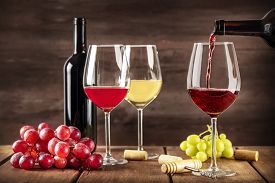 Wine Tasting. Red Wine Poured Into A Glass From A Bottle With Copy Space And Other Glasses And Grape