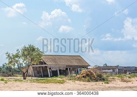 Landscape With An Old Rickety Shed, A Bunch Of Garbage And A Tree Against A Blue Sky With Clouds