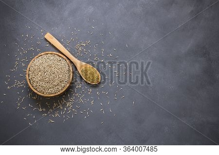 Pile Of Dry Caraway Spice With Ground Caraway Powder In Wooden Spoon. Healthy Food Cumin Spice Conce