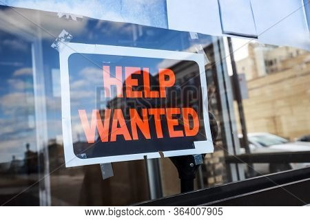 Reflection of a silhouette of a man looking at a help wanted sign in a business window, economy concept, shallow focus on middle of sign