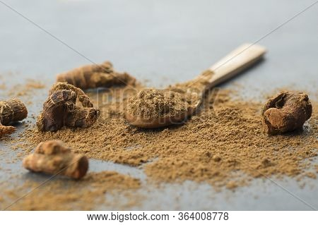 Galangal Root And Galanga Powder In Wooden Spoon On Rustic Table. Healthy Spice Concept (alpinia Off