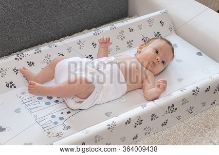 Happy Baby Girl Lying On Diaper Changing Pad, Wearing A Diaper. Cute Adorable Baby Is 3 Months Old.