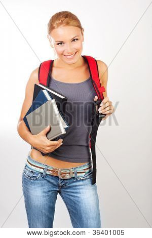 Cheerful student girl with textbooks isolated on white background, beautiful teenager with red backpack in studio, back to school, happy schoolgirl, knowledge and education concept