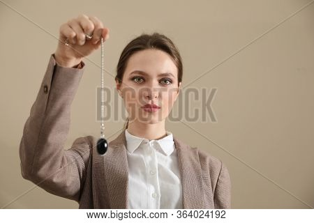 Psychotherapist With Pendulum On Beige Background. Hypnotherapy Session