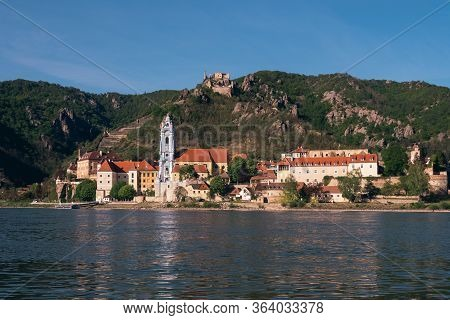 Duernstein Cityscape With Blue And White Baroque Abbey Church Tower And Kuenringer Castle, Located O
