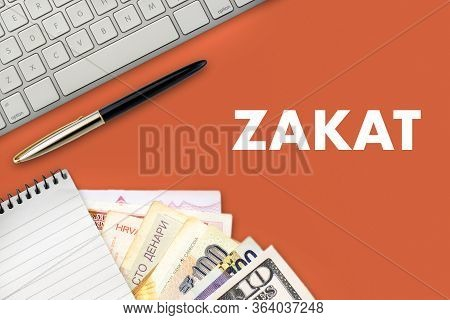 Zakat (islamic Tax)  Text With Notepad, Keyboard, Multi Banknote Or Currency And Fountain Pen On Ora